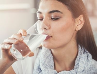 woman drinking filtered water from a glass